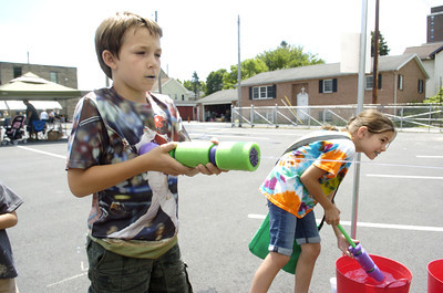 St. Monica School students Dominic Cecco, 9, left, and Sarah Kelsey, 9, play a game at the school's carnival on Thursday.