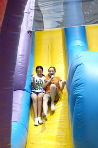 Best friends Kathy Tran, 12, left, and Sabrina Sinsel, 13, go down a slide on Thursday during St. Monica's school carnival in Sunbury.