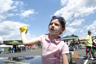 Anna Keer, 5, throws a softball at a dunk tank Thursday afternoon at St. Monica's school carnival.