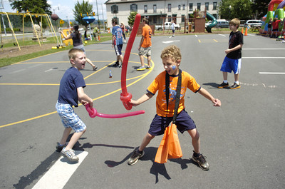 St. Monica students Connor Andretta, 7, left, and Collin Kline, 9, have fun with their balloon swords at the school's carnival on Thursday.