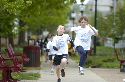 St. Monica students Michael Morach, 11, left, and Patrick Rooney, 13, race around Cameron Park in Sunbury on Friday morning.