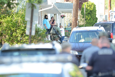 A police officer with a long rifle on his back walks past a house on Fifth Street in Northumberland during a standoff on Monday evening.