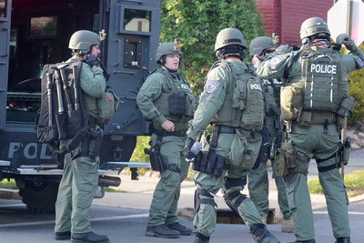 Police officers gear up during a standoff along Orange Street in Northumberland on Monday evening.