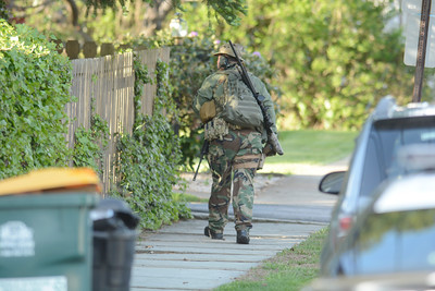 A police officer with a long rifle looks over a fence as he walks up fifth street in Northumberland on Monday during a standoff.