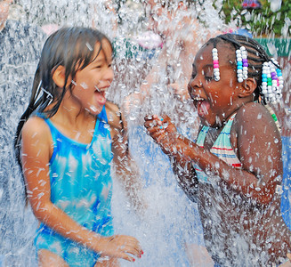 Amanda August/For The Daily Item Erica Leitzel, 7 of Sunbury, and Nyasia Vincent, 6 of Sunbury, play in one of the shooting fountains at the Oppenheimer Pleasure Grounds during the kickoff event to the Sunbury Celebration on Thursday night.