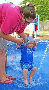 Amanda August/For The Daily Item Kara Greene, of Sunbury, helps her son Callan, 7 months, play in the water fountain at the kickoff event to the Sunbury Celebration at the Oppenheimer Pleasure Grounds on Thursday night.