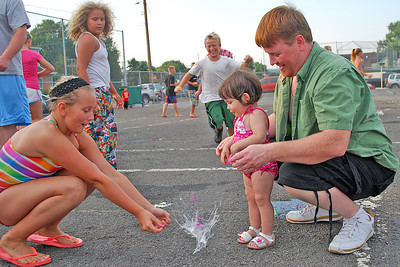Amanda August/For The Daily Item Gabby Hauptimann, 11, and her father Christopher watch as the balloon her sister Summer, 18 months, explodes on the ground during the kickoff event of the Sunbury Celebration at the Oppenheimer Pleasure Grounds on Thursday night.