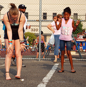 Amanda August/For The Daily Item Two girls react to the dropping of an egg during the egg toss competition at the Oppenheimer Pleasure Grounds on Thursday night during the Sunbury Celebration.