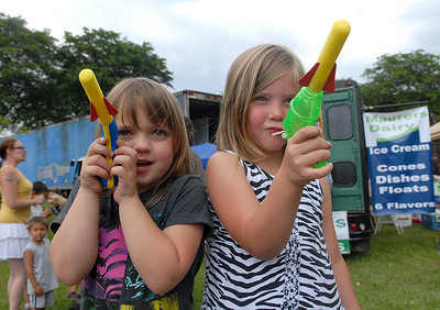 Cousins, Sydney Sinko, 5, and Makya Michaels, 5, both of Sunbury aim for their mothers during the annual Sunbury Fireman's Festival Saturday June 9, 2012.