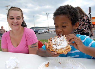 Isaiah Fetter, 6, of Sunbury takes a bite out of his funnel cake under the watchful eye of his mother, Stephanie, at the Sunbury Fireman's Festival Saturday June 9, 2012.