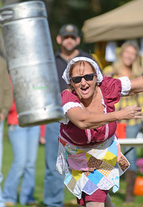 Patty Clement, of Selinsgrove, participates in the keg toss at the Sunbury Social Club's Oktoberfest on Saturday afternoon on Packer Island.