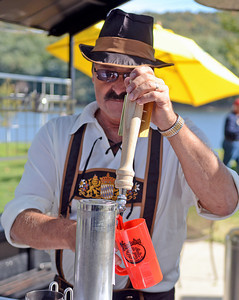 Steve Lahr, of Northumberland, taps a beer at the Sunbury Social Club's Oktoberfest on Packer Island on Saturday afternoon.