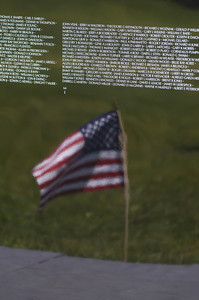 A flag is reflected in the traveling Vietnam Memorial wall on Saturday in Union Town.