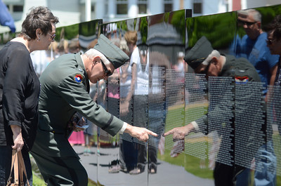 Diane and Richard Sholly, Beavertown, look for names they recognized in the traveling Vietnam Memorial Wall before the start of Saturday's ceremony for it in Union Town. Richard Sholly is an army veteran and served in Vietnam in the 9th infantry division.