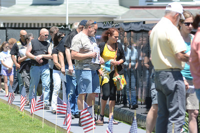 A crowd of people walk along the traveling Vietnam Memorial wall during a ceremony on Saturday in Union Town.