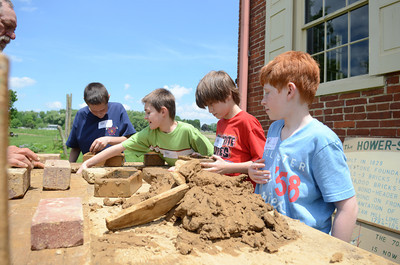 Warrior Run fifth grade students Brandon Bataman, left, Dustin Tyson, Trace Barlet, and Matthew Eckroth, make clay bricks by hand during their On Site Day on Wednesday at the Hower-Slote House.