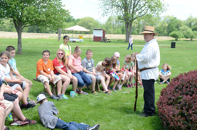 Warrior Run fifth grade students listen to Mark Keithan talk about a Kentucky Rifle on Wednesday during their On Site Day.