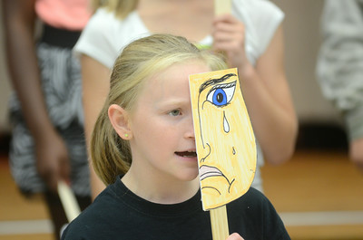 Cara Bossley, 10, holds up a mask to cover half her face while rehearsing for What's Shakin', Shakespeare? on Tuesday. It's a DIVA production put on at the James F. Baugher Elementary School in Milton by Milton Elementary School students.