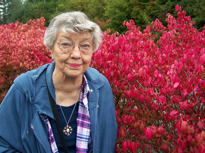 Mom next to the vibrant bushes growing in the parking lot for Snoqualmie Falls.