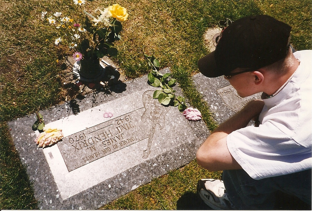 """Since this picture was taken in 1997, Jimi Hendrix's grave has been relocated to the side of the cemetery (where it's easier for fans to visit without disturbing the other graves) and his family created <b><a target=""""_new"""" href=""""http://www.deadbluesguys.com/image_pages/hendrix_jimi_im/hendrix_jimi_10.htm"""">a much larger monument.</a></b> Josh and I wanted to leave some sort of offering, so I placed a couple of Tylenols I had in my camera bag on the headstone.  Given the life he led, I figured Jimi would appreciate that!  :-)"""