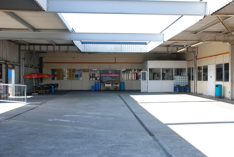 close up shot of the area at the bottom of the platform with the Ferry <br /> <br /> Terminal entrance on the right through the white door and the exit to <br /> <br /> the Car Park on the left where the railing is just viewable in shot