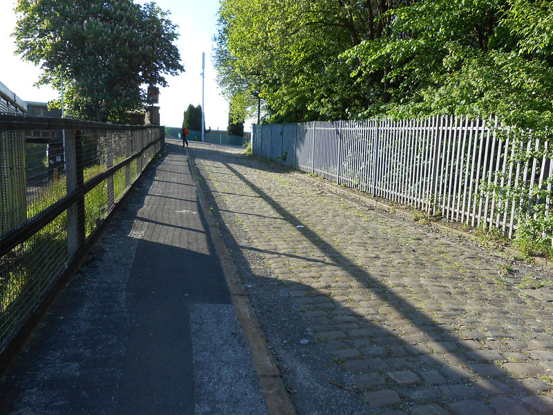PIc by Liz <br /> <br /> looking up towards the Main road Rake Lane from the Bottom of the Access road to the left of her is the gate to access the platform