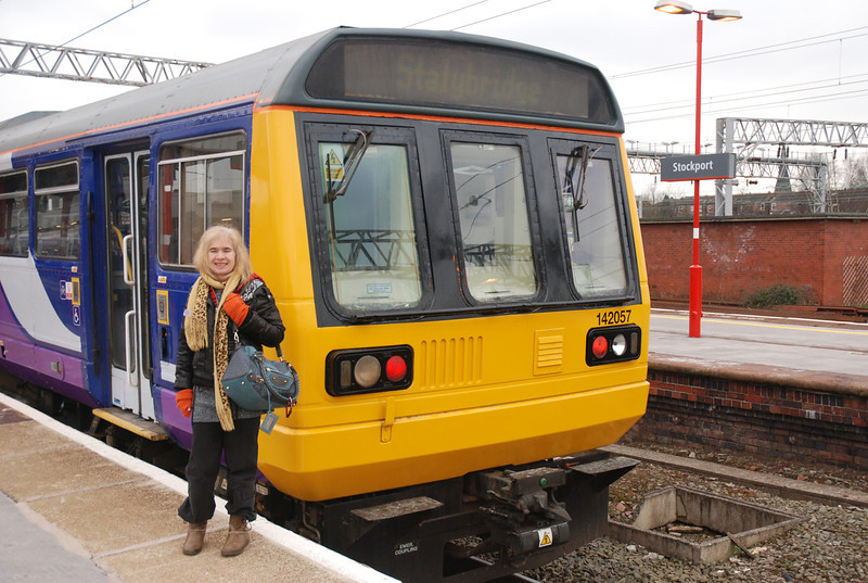 side on of Liz with the Stockport station sign in Back ground