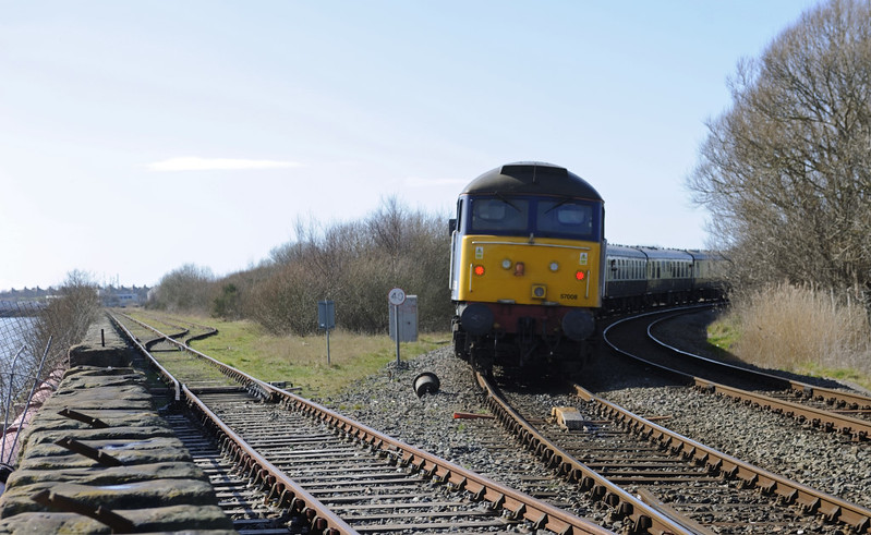 57008, 1Z22, Salthouse Junction, Barrow-in-Furness, 21 March 2015 2 - 1304.  The Cumbrian Docker heads away from the camera towards Workington.  This used to be a very busy location and the line to Ramsden dock was double track.  The scrub vegetation marks the site of Barrow loco shed, closed in 1977 and demolished.