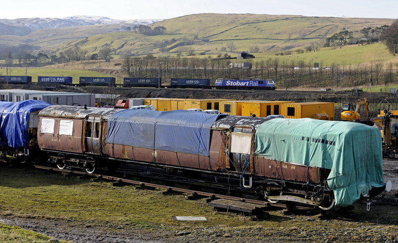 LMS 29896 & 92017 Bart the Engine (4S43), Tebay, Mon 30 January 2012 - 1206.  DB Schenker's late running Tesco Express passes the two preserved class 502 EMUs stored at Tebay.  28361 is just visible at left.