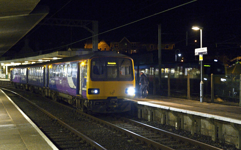 144022 (2H94) & 350xxx (1M91), Carnforth, Sat 10 January 2015 - 1826.  Northern's 1639 Leeds - Morecambe calls at Carnforth as FTPE's 1612 Edinburgh - Manchester Airport passes.