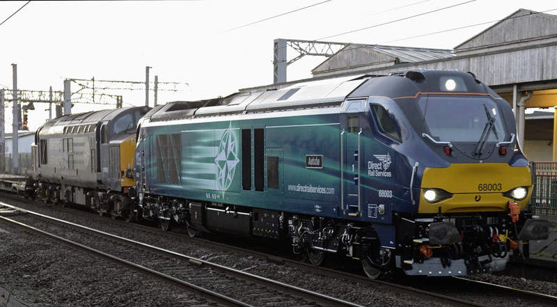 68003 Astute & 37605 (DIT), 4Z37, Carnforth, Fri 2 January 2015 - 1556.  A novel loco combination on a Daventry - Motherwell move with empty flat wagons.  68003 had joined 37605 at Basford Hall.  The train had left Crewe 66 minutes late, but passed Carnforth 100 early!  The ten wagon consist was reported as 6849094139 IKA, 7049010622 IDA, 6849090418 IKA, 6849093982 IKA, 6849091549 IKA, 6849094816 IKA, 6849430754 IKA, 6849094527 IKA, 6849099344 IKA & 6849094295 IKA.