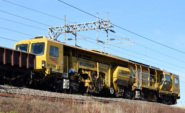 DR 77904, 6K05, Carnforth, Thurs 9 March 2017 - 1347.  Network Rail's Plasser & Theurer USP 5000 RT ballast regulator hitches a lift on the rear of DRS's 1103 Carlisle yard - Basford Hall departmental, hauled by 66430.