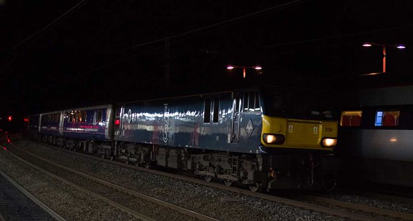92038, 1M16, Lancaster, Tues 31 January 2017 - 0505.  The 2044 Inverness - Euston Caledonian Sleeper, running 54 late.  Several trains on the Highland main line were delayed by points problems at Carrbridge.  1M16 had left Aviemore 104 late after leaving Inverness on time.  It had been hauled by 67010, hired by GBRf to cover for absent 73s.  The 14 coaches from Edinburgh including the Fort William and Aberdeen portions were reported as 9809, 1210, 10723, 10520, 10610, 10598, 10507, 9806, 6701, 10714, 10561, 10504, 10544 & 10523.  The sleeper is passing 390157 Chad Varah, which was working Virgin's 1R07 0513 Lancaster - Euston.