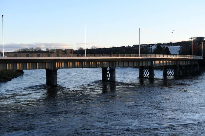 Greyhound bridge, Lancaster, 9 December 2018.  The A6 / A589 bridge was refurbished in 2018.  It used to carry the Lancaster Green Ayre - Morecambe line.  The River Lune flows towards the camera, running high after a week of rain.