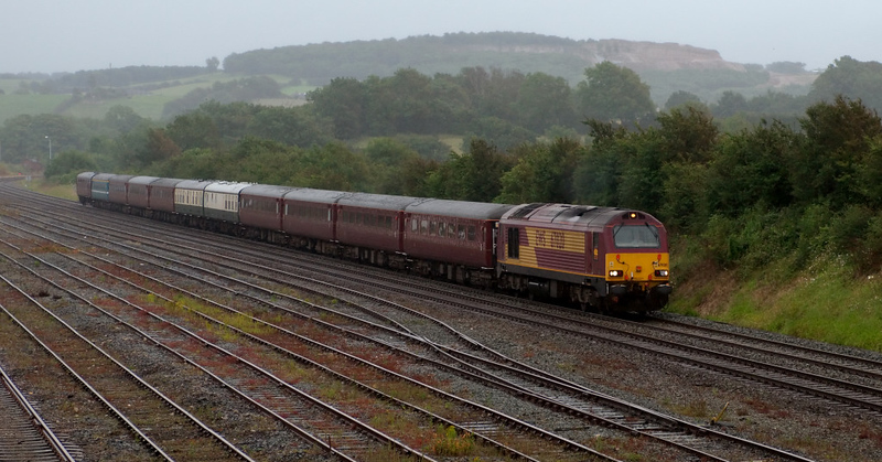 67020, 1Z57, Carnforth, 11 July 2008 - 0921    In pouring rain, the support train for the annual Three Peaks Challenge fund raising event for the Railway Children charity leaves Carnforth en route from Bangor (for Snowdon) to Ravenglass (for Scafell Pike).  It will then go to Fort William for Ben Nevis.