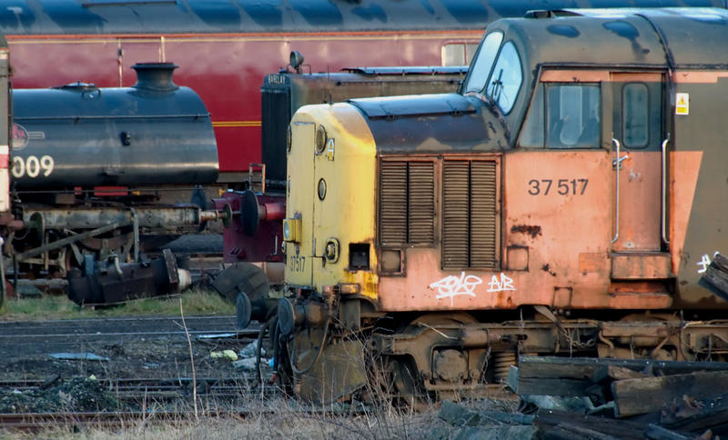 68009 & 37517, Carnforth, 5 April 2008   The saddle tank of the privately-owned 0-6-0ST is on a wagon, next to the Barclay diesel.
