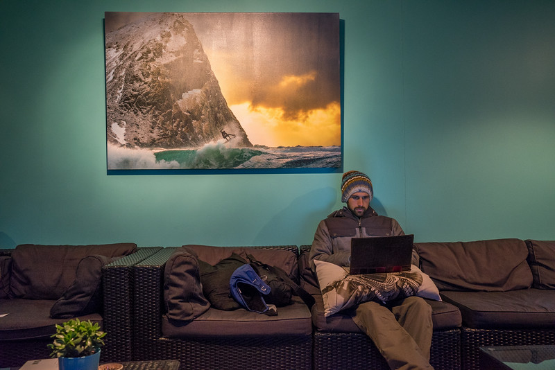 His photgraphy known around the world, a Chris Burkard original canvas sits on the wall above Surfer Chadd as he checks his email in the warmth of the main cabin as the snow starts to fall outside at a more rapid pace.