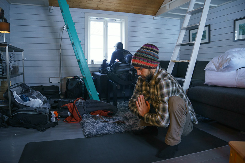 Chadd practices his morning yoga as Brett glances out the window to check the first days weather, which turned out to be full of snow.