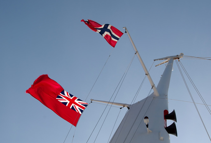 Norwegian courtesy flag, QE2, off Trondheim, 5 June 2008   The flag and the red ensign catch the evening sun.