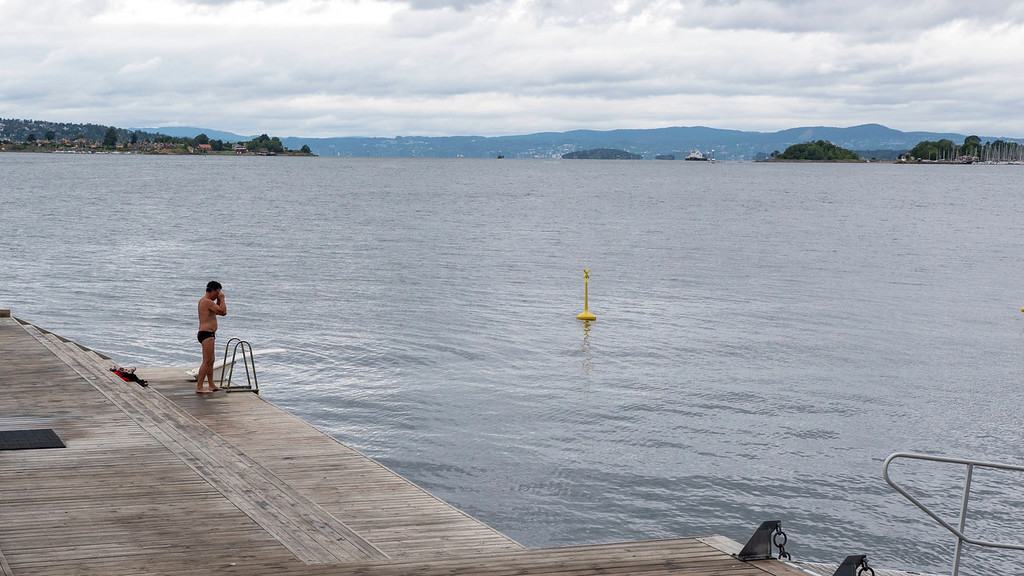 Man going for a swim at Tjuvholmen in Oslo Norway