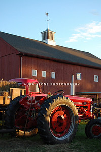 A red tractor in front of a barn at the Woodstock Fair, Woodstock, CT.