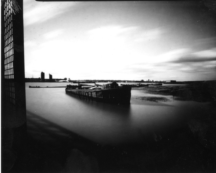 This is the first of 2 photos taken from the same place within 5 minutes of each other, this one was taken on positive paper (ISO 3) with an exposure of 2min 15 sec. It is of a concrete barge, one of many which have been left along the banks of the Thames at Rainham, Essex. Originally used to ferry troops for the D Day landings but were left here in1953 to help protect the banks from the North Sea floods that devastated the East Coast of England as well as Belgium, Netherlands and Scotland.