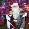 Khymber (left) and Keira Thompson pose with Santa next to the city's Christmas Tree at Darius Miller Park.
