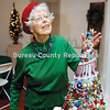 """Jeanne O'Melia admires and puts finishing touches to the tree shemade for the Prairie Arts Center's Christmas Mini-Tree Festival. The tree was called """"Peace on Earth."""""""