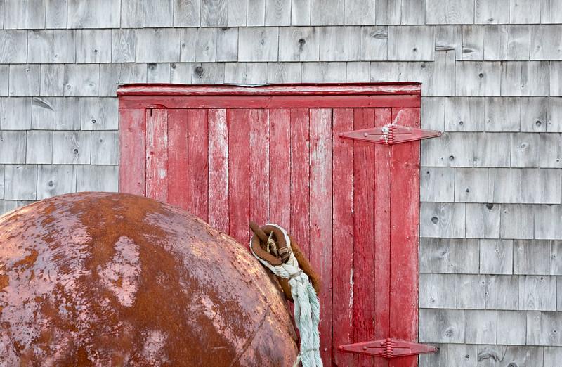 Metal Buoy resting beside lobster shack near Grand Harbour on Grand Manan Island