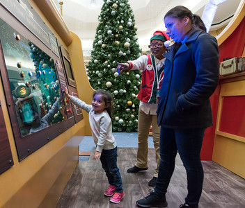 111016  Wesley Bunnell | Staff  Luz Sofia Valentin, age 3, picks which route Santa should take with the help of mom Nidia Caraballo and one of Santa's elves during Santa's Flight Academy at the Westfarms Mall on Thursday afternoon.