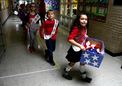 11/10/2016 Mike Orazzi | Staff Sienna Torres carries the American flag in a box while on her way to the Edgewood School's Veterans Day program in Bristol Thursday morning.