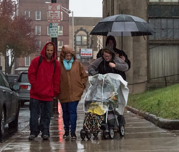111516  Wesley Bunnell | Staff  Walking through the downpour on Washington St Tuesday afternoon are , from left, Jose Leon, Windy Ponce, Shelimar Gonzalez pushing her son Joshua Gonzalez-Ponce & Christian Feliberty holding the umbrella over Windy.