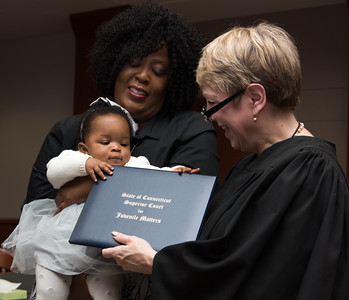 111816  Wesley Bunnell | Staff  Cedrica Titus holds her adopted daughter Dream Arden Titus as she reaches for her adoption decree held by the Honorable Judge Abery-Wetsone in New Britain Family Court on Friday afternoon. Friday was National Adoption Day across the country.