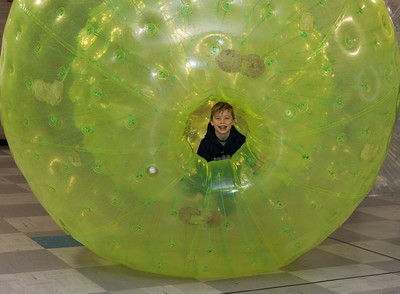 112116  Wesley Bunnell | Staff  Edgewood Elementary School held a hamster themed day which included a human hamster ball for the staff and students to enter. Luke Viens, a student in Ms. Schulitz's fourth grade class, smiles through the opening in the hamster ball during his turn.